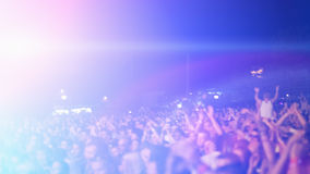 Concert crowd. In front of violet stage-lights Stock Photo