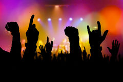 Concert crowd hands supporting band on stage. Concert crowd hands supporting rock and roll band performing live music on stage, silhouettes of young people on Royalty Free Stock Image