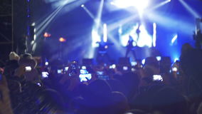 Concert Crowd at Music Festival. Crowd people dancing Rock concert, weighed, applauds, raises his hands up and photographed, filmed concert on the phones and stock footage