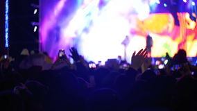 Concert Crowd at Music Festival. Crowd people dancing Rock concert, weighed, applauds, raises his hands up and photographed, filmed concert on the phones and stock video