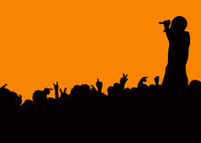 Concert crowd wave. Crowd silhouette at music concert with artist singing with orange background Stock Photo