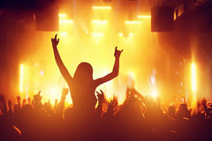 Concert, disco party. People having fun in night club. Concert, disco party. Woman silhouette with hands up in foreground and people having fun in night club royalty free stock photos