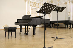 Concert grand piano on a scene. Grand piano and lecterns on a concert hall scene Stock Image