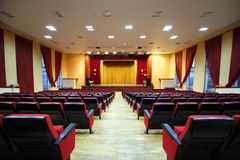 Concert hall and empty stage. Many rows of red seats and stage Stock Image