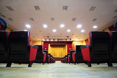 Concert hall and empty stage. Many rows of red seats and stage with yellow curtain; view from floor Royalty Free Stock Image