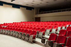 Concert Hall Seats. Sets of red seats on a concert hall. Lighting with spot lights on the top with a dark balcony section Stock Photo