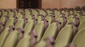 Concert Hall - spectators come into green chairs - de-focused time-lapse. Close up Royalty Free Stock Photos