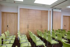 Concert hall with stylish green chairs, wooden cabinets and door. Side view shot of concert hall with stylish green chairs, wooden cabinets and door Stock Image