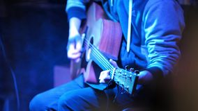 Concert in jazz club - musician plays acoustic guitar. Close-up telephoto shot stock video footage