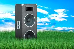 Concert loudspeaker in green grass against blue sky, 3d renderin. Concert loudspeaker in green grass against blue sky, 3d Royalty Free Stock Images