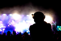 Concert man silhouette. Silhouette of a man in the crowd next to concert lights Stock Photos