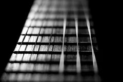 Concert music instrument guitar strings in black white silver. Closeup of the string instrument for classic rock pop isolated on black background Stock Photo