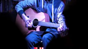 Concert in night club - musician on concert plays acoustic guitar