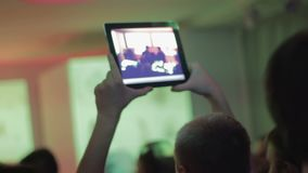 Concert in the nightclub, people dancing, man filming popular band with tablet stock video