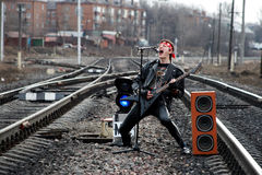 Concert At The Railway Tracks. The young rock musician plays guitar on the track on the background of the city Royalty Free Stock Photos