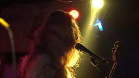 Musician performs solo during concert in night club. Concert rock band performing on stage with singer performer, guitar stock footage