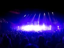 Concert scene with standing crowds facing the stage. Bright stage lights. royalty free stock photo