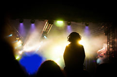 Concert silhouette. Silhouette of a man in the crowd next to the colourful concert lights with head phones Royalty Free Stock Image