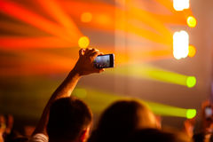 Concert Snapshot. Someone talking a picture during a concert with a phone. Rays of light music, the hand holding a touchscreen smartphone stock images