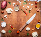 Concert vegetarian food Potato onion cauliflower garlic cherry tomatoes mushrooms seasoning hot red pepper and knife frame with sp Royalty Free Stock Image