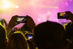 Concert visitor shoots video. On a smartphone Royalty Free Stock Photo