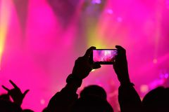 Concert visitor shoots video. On a smartphone Stock Photo
