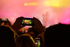Concert visitor shoots video. On a smartphone Stock Photos