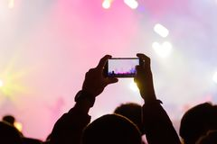 Concert visitor shoots video. On a smartphone Royalty Free Stock Images