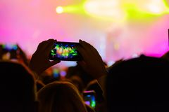 Concert visitor shoots video. On a smartphone Stock Photography