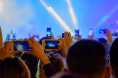 Concert visitor shoots video. On a smartphone Royalty Free Stock Photography