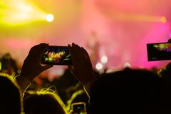 Concert visitor shoots video. On a smartphone Royalty Free Stock Image