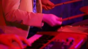 Concerto da faixa na fase em discolights foco de transferência do baterista ao jogador de teclado Mãos dos músicos no filme