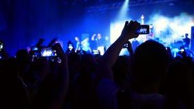 Concerto da música do smartphone dos povos vídeos de arquivo