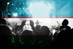 Concerto di musica in diretta con il mescolamento della bandiera dell'Uzbekistan sui fan Fotografie Stock Libere da Diritti