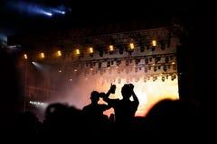 Concerto rock, siluette della gente felice che solleva sulle mani Fotografia Stock Libera da Diritti