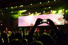 Concerto rock, siluette della gente felice che solleva sulle mani Fotografie Stock Libere da Diritti