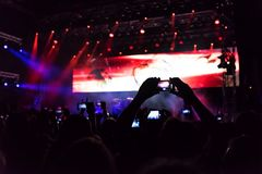 Concerto rock, siluette della gente felice che solleva sulle mani Fotografie Stock