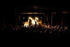 Concerto, silhuetas dos povos felizes que levantam acima as mãos Fotografia de Stock Royalty Free