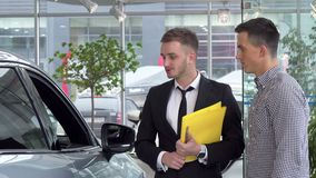 Concesionario de coches amistoso que ayuda a su cliente masculino que elige el automóvil para comprar metrajes