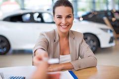 Concesionario de coches de sexo femenino en la sala de exposición Fotos de archivo libres de regalías