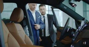 Concesionario de coches que muestra el coche al cliente imagen de archivo