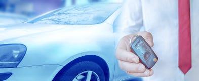 Concessionário automóvel com uma chave Fundo do conceito do auto negócio e do arrendamento fotografia de stock
