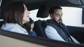 Concessionário automóvel de visita A família bonita é de fala e de sorriso ao sentar-se em seu carro novo video estoque