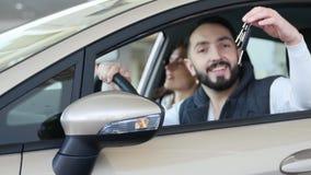 Concessionário automóvel de visita A família bonita é de fala e de sorriso ao sentar-se em seu carro novo o homem novo mostra o d vídeos de arquivo