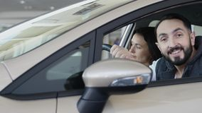 Concessionário automóvel de visita A família bonita é de fala e de sorriso ao sentar-se em seu carro novo o homem novo mostra o d video estoque