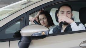 Concessionário automóvel de visita A família bonita está sorrindo ao sentar-se em seu carro novo O homem novo mostra o dedo acima vídeos de arquivo