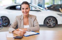 Concessionário automóvel fêmea na sala de exposições Fotos de Stock