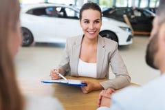 Concessionário automóvel fêmea na sala de exposições Foto de Stock Royalty Free