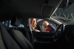 Concessionario auto di visita Il capo vendite bello sta sorridendo mentre il bello cliente sta firmando le carte fotografie stock