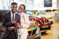 Concessionnaire automobile de visite couplez tenir la clé de leur nouvelle voiture, regardant l'appareil-photo image libre de droits